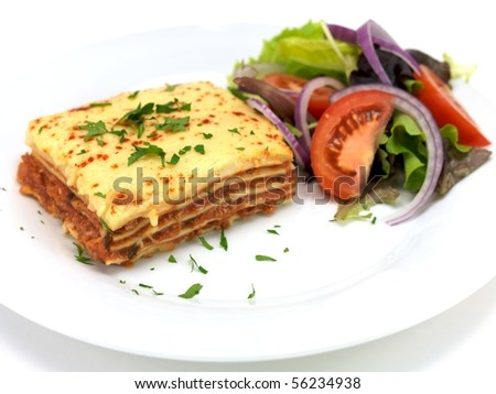 Lasagne plated up with a salad and isolated against a white background - stock photo