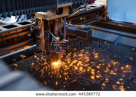 Laser cutting machine operates metal detail causing bright sparks