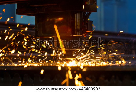 Laser cutting machine operates metal part causing bright sparks (close-up)
