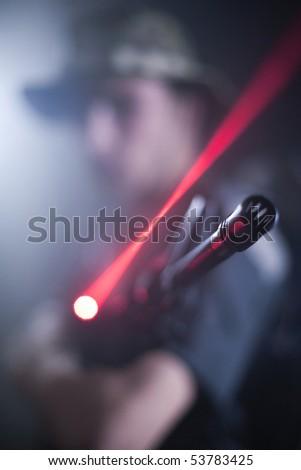 Laser gun being held by soldier. - stock photo