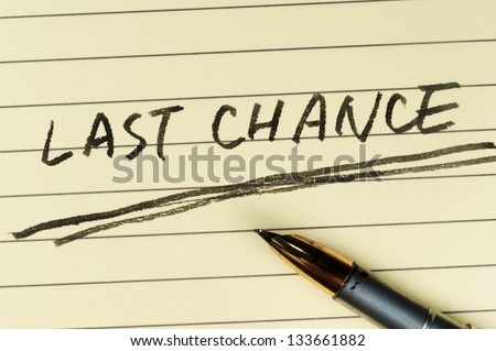 Last chance words written on lined paper with a pen on it
