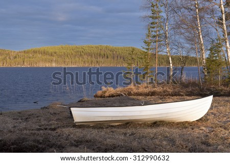 Last lit over a forest across a lake. The Nordic taiga, ridges of trees, spruce, fir in endless areas. Evergreen in yellow, orange. Boat this side. - stock photo