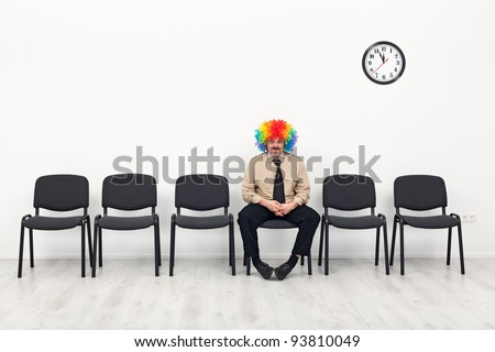 Last man standing - waiting concept with clown in business outfit - stock photo