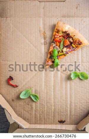 last one slice of homemade vegetarian  pizza in box from above - stock photo