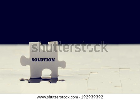 Last puzzle piece with the word - Solution - standing upright on top of a jigsaw puzzle with just the one piece missing to complete it, toned instagram effect. - stock photo