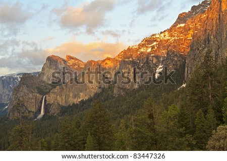 Last rays of sun off the snow and cliffs above Bridalveil Falls in Yosemite National Park, California - stock photo