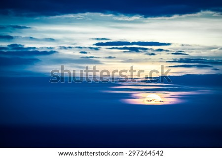 last seconds of a distant sunset over the ocean - stock photo