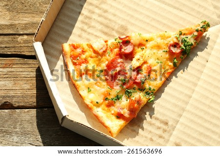 Last slice of pizza on wooden table - stock photo