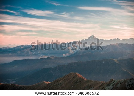 Last sunlight behind the majestic peaks of M. Viso (3841 m), Italian - French Alps, viewed from distant. Mist in the valley below, autumnal landscape. Vignetting and retro styled film cross processing - stock photo