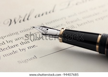 Last will and testament document with closeup on fountain pen with signature line. Critical focus on fountain pen. - stock photo