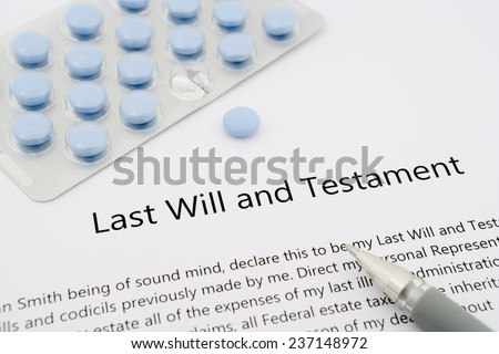 last will and testament with blue pills and grey pen - stock photo