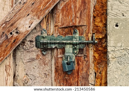Latch with padlock on a old wooden door - stock photo