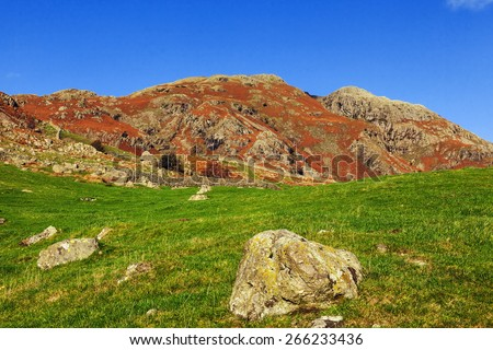Late afternoon autumn sun on the mountains of the Upper Langdale Valley. Late afternoon Autumn sunlight shows the impressive mountains of the Langdale Valley to good effect. - stock photo