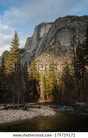 Late afternoon light partially illuminates Half Dome as it rises more than 4,730 feet from the floor of the valley in Yosemite National Park, California. This granite dome is popular among  climbers. - stock photo
