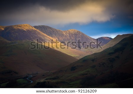 Late afternoon sunlight spills through winter clouds in Mountains - stock photo