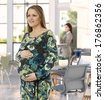 Late pregnant woman standing at office, touching belly, smiling. - stock photo