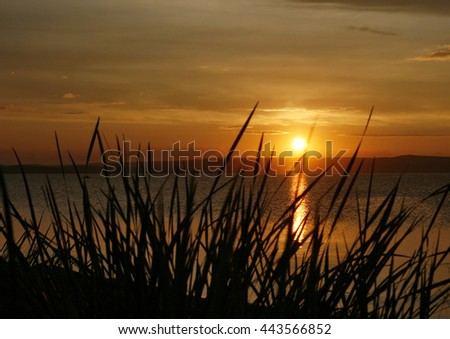 Late summer evening on the lake. The sun sets behind the horizon. - stock photo