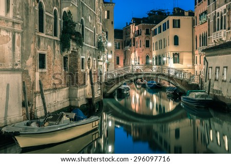 Lateral canal and pedestrian bridge in Venice at night with street light illuminating bridge and houses, with docked boats, Italy. Toning in cool tones - stock photo