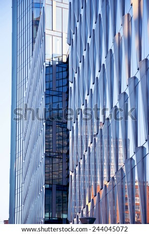 lateral view of a modern skyscraper with reflections on glass walls - stock photo