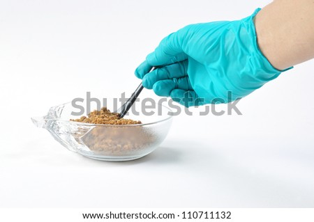 Latex Glove For protect on hand and spoon in a glass cup with brown sugar.