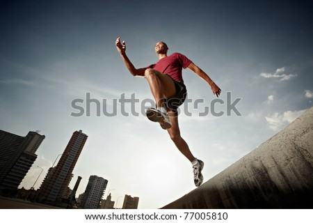 Latin american athlete running in Havana, Cuba. Horizontal shape, full length, low angle view - stock photo