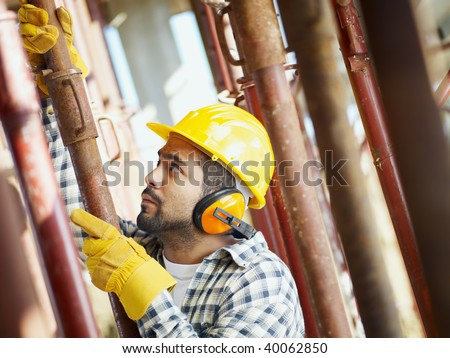 latin american construction worker fastening girder. Side view - stock photo