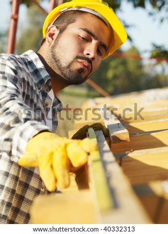latin american construction worker on house roof with measuring tape. - stock photo