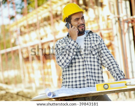 latin american construction worker talking on mobile phone. Copy space - stock photo