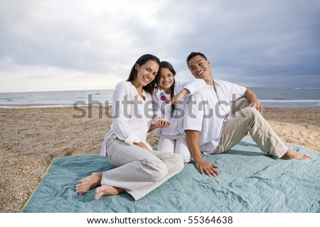 Latin American family with 9 year old girl sitting on blanket at beach - stock photo