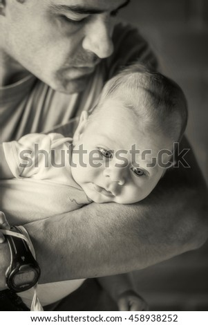Latin American Father Holding Newborn Baby Boy In His Arms, Monochrome Shoot  - stock photo