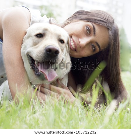 Latin American girl embraces her dog in the park on the background of the house - stock photo
