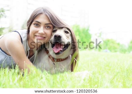 Latin American girl embracing her dog in the park on the background of the house - stock photo