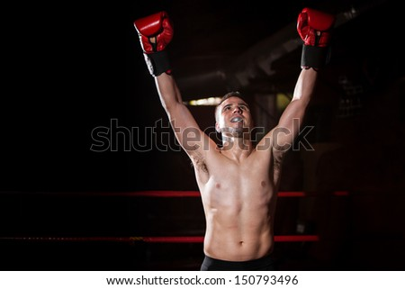 Latin Boxer raising his arms in sign of victory with a lot of copy space on the side - stock photo