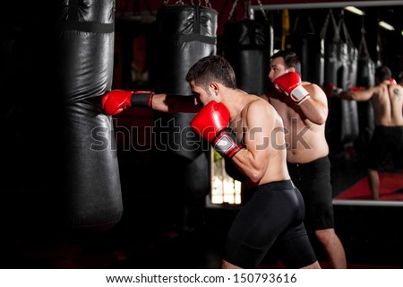 Latin Boxers doing some training on a punching bag at a gym - stock photo