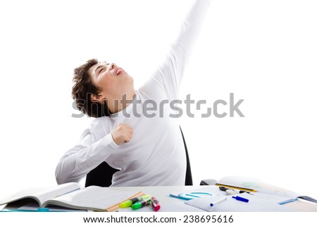 Latin Caucasian Teenager boy sitting while doing homework is happy and poses as a superhero going to fly away with left arm high towards the sky - stock photo