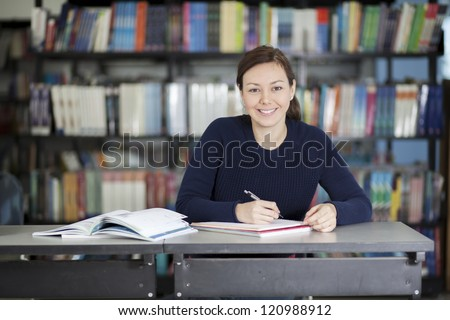 Latin college student doing homework at the library - stock photo
