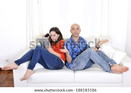 Latin couple sitting on couch or sofa at living room being boyfriend frustrated , angry and girlfriend always busy with tablet and mobile phone in relationship problems due to internet addiction - stock photo