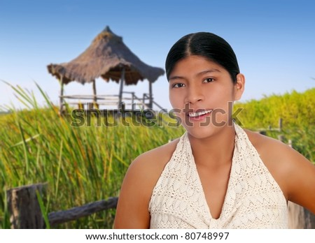 Latin hispanic mayan woman portrait in wetlands with hut background  [Photo Illustration]