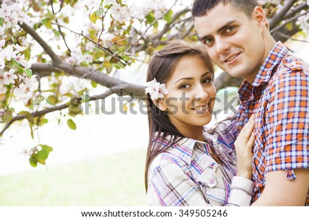 Latin hispanic Young adult beautiful couple embracing in spring park against the background of a large branch of apple blossoms. man and woman in love looking at camera with smiley faces - stock photo