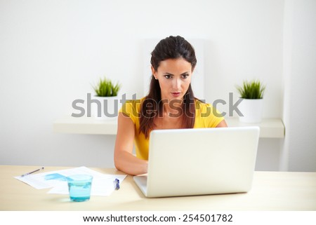 Latin lovely company secretary using computer for work in her office - stock photo