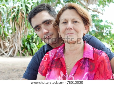 Latin man and older woman in a park - stock photo