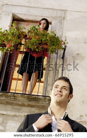 Latin man with her girlfriend on a balcony - stock photo
