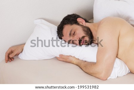 latin man with naked torso lying in bed and sleeping