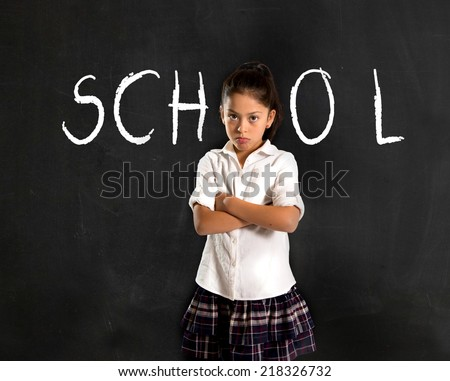 latin moody little girl in uniform standing upset in front of blackboard with school written with chalk in I hate studying and learning is boring concept  - stock photo