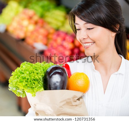 Latin woman grocery shopping looking very happy