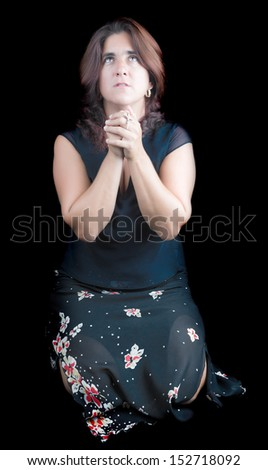 Latin woman praying and holding a small crucifix (isolated on black) - stock photo
