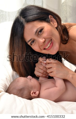 Latin woman sharing with her baby born on bed.Enjoying my baby boy Parent and little kid relaxing at home. Family having fun together. Bedding and textile for infant nursery.  - stock photo