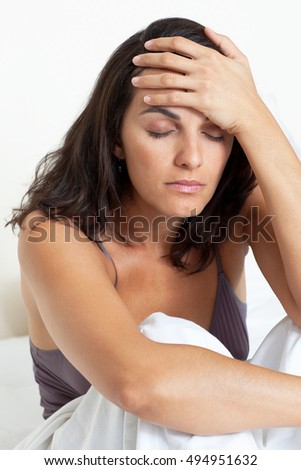 Latin woman with headache sitting in bed