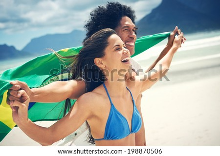 Latino hispanic couple are Brasil fans and hold flag having fun together - stock photo