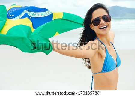 Latino woman with Brasil flag laughing and smiling in support of Brazilian soccer fan - stock photo